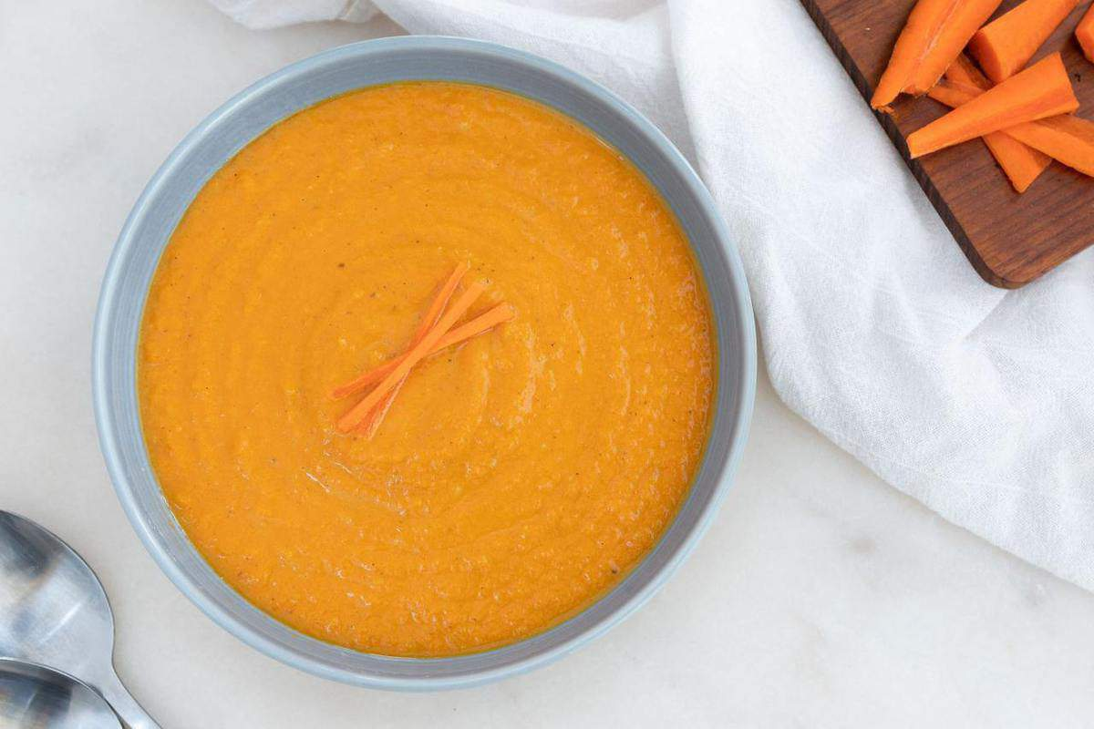 spicy carrot soup in blue bowl against white background with cutting board in the background
