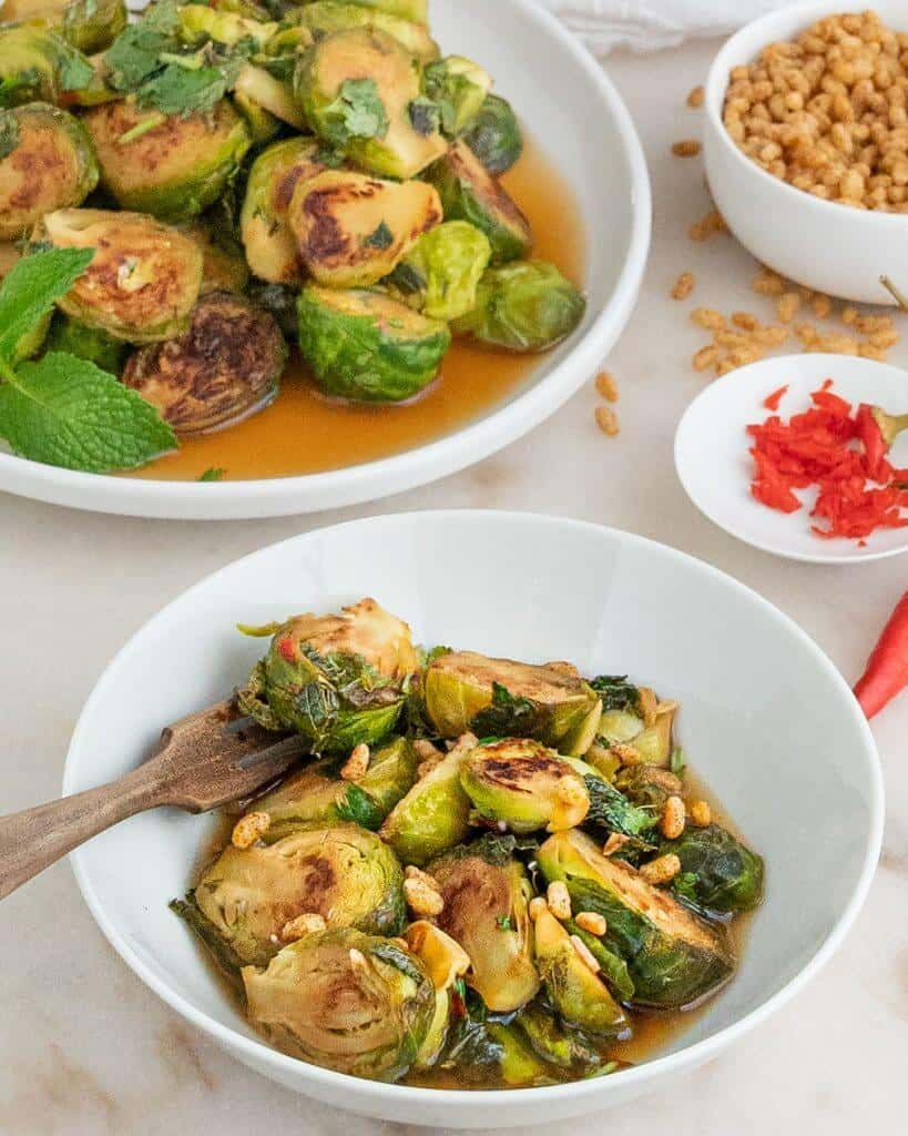 finished spicy mint brussels sprouts plated on a white bowl with several bowls with ingredients in the background