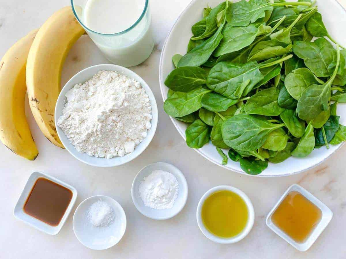 Ingredients to make spinach banana pancakes laid out on a surface