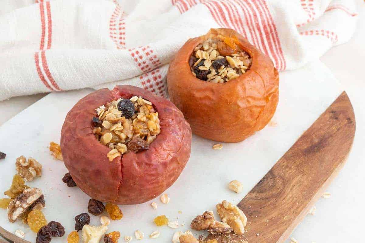 two stuffed baked apples on a white cutting board