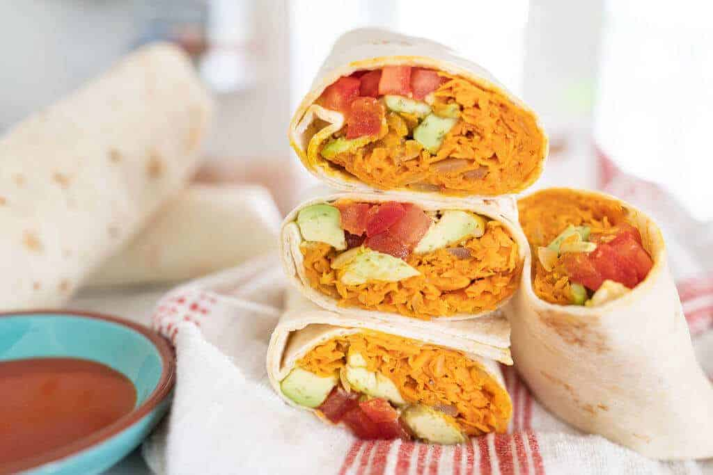 Sweet Potato Burritos stacked on a white and red towel with ingredients in the background