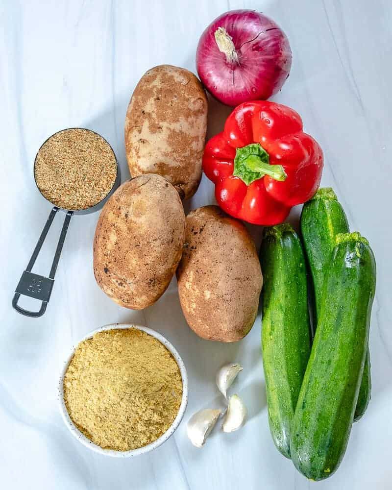 3 potatoes, 1 red bell pepper, 3 zucchinis, 1 onion and spices in a white background
