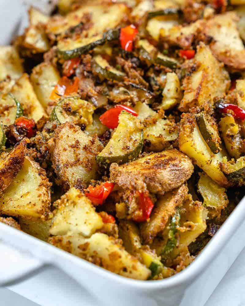 zucchini potato casserole in a white baking pan