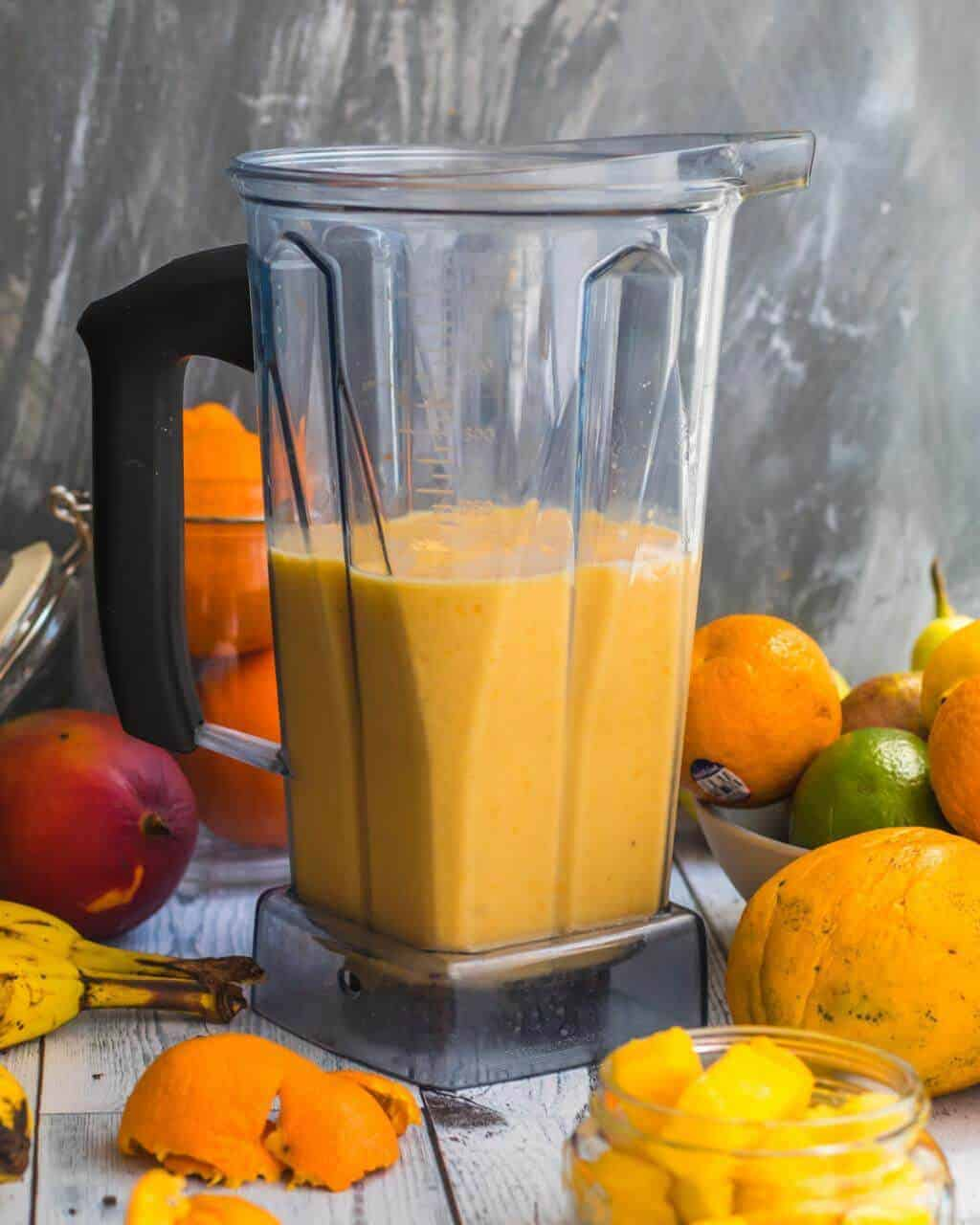Vitamix blender filled with the citrus mango smoothie and surrounded by different tropical fruits
