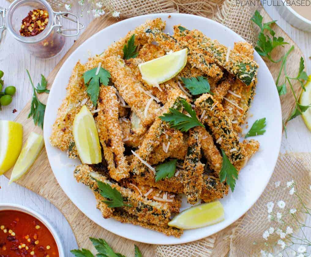 white plate of zucchini fries with severl ingredients in the background