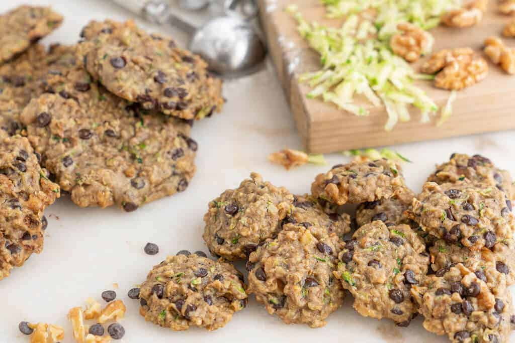 several banana zucchini cookies on a light colored surface with a cutting board and more cookies in the background