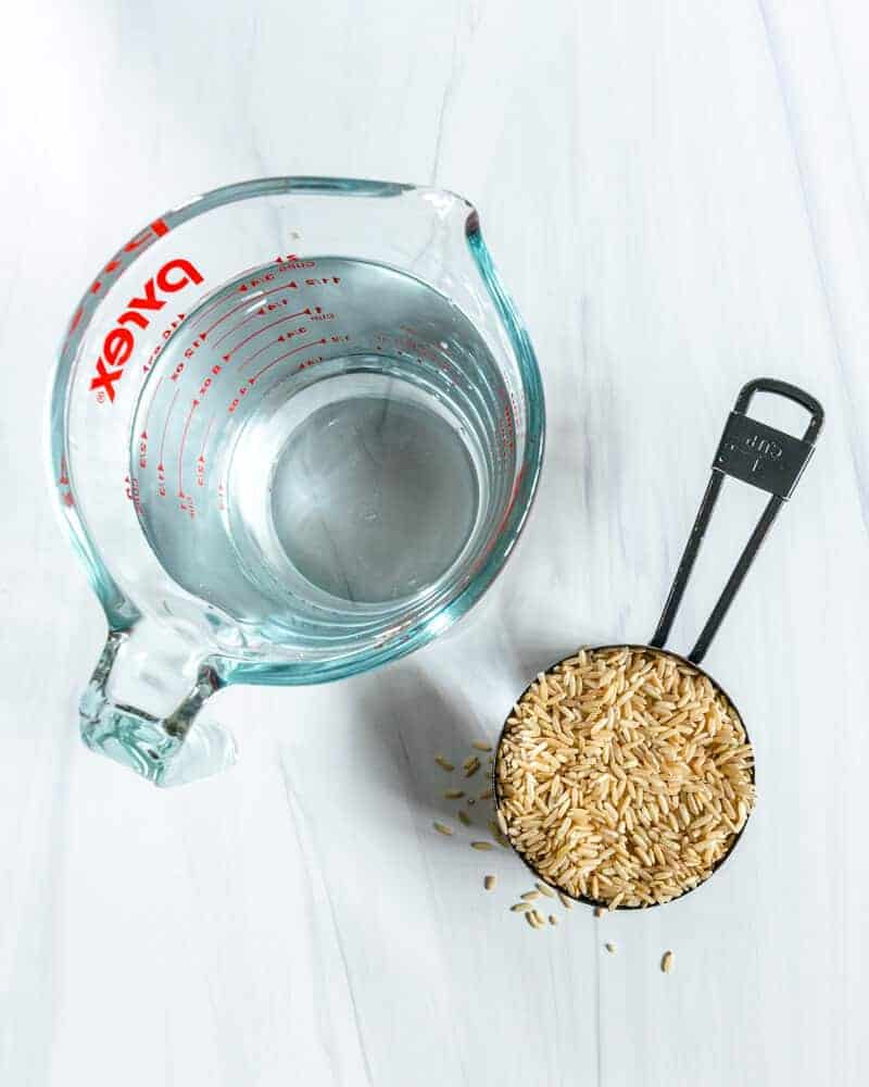 Liquid Measuring Cup with Water and a Cup Measurement With UnCooked Brown Rice On a Marble White Surface