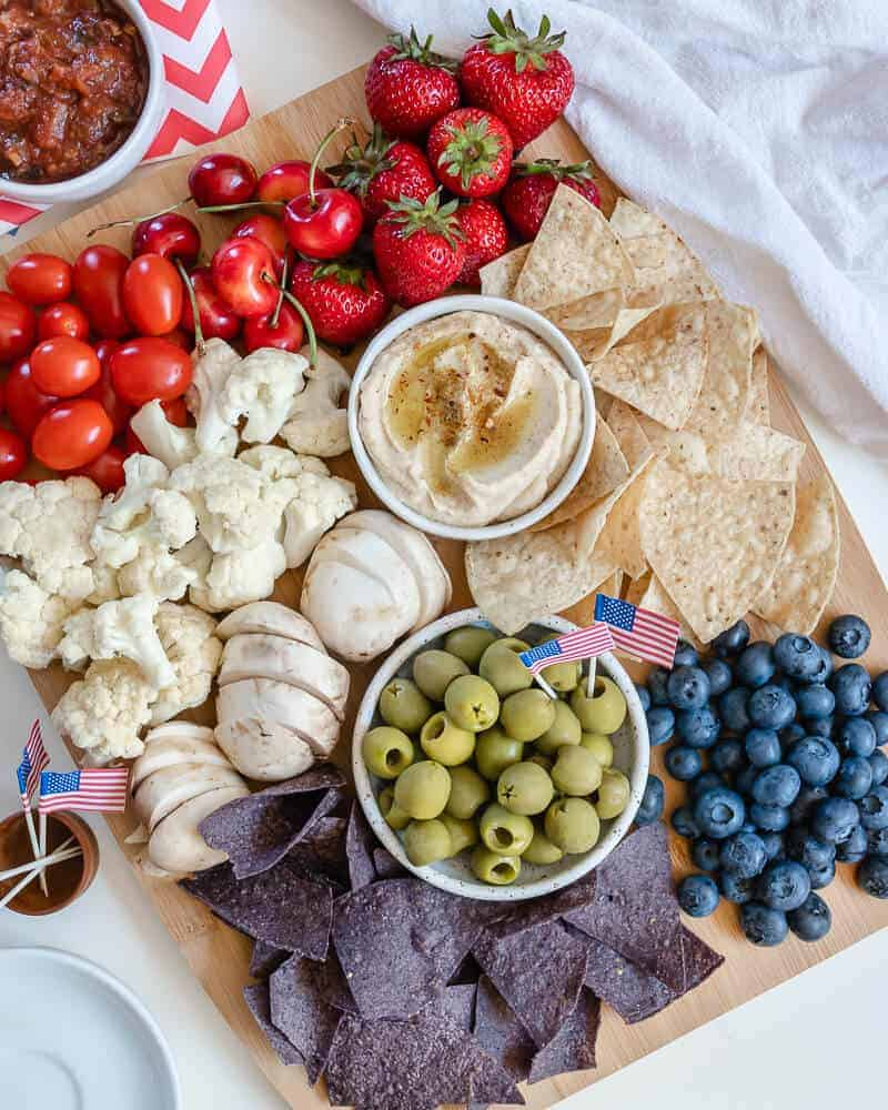 colorful charcuterie board with chips, olives and tomatoes
