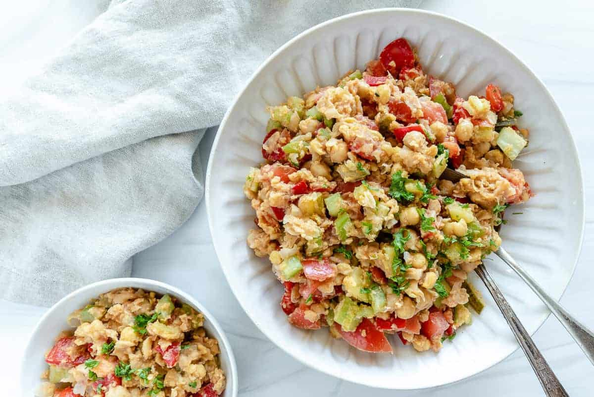 two white plates of chickpea salad in a white background
