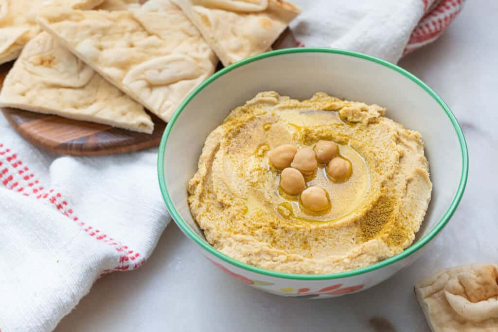 finished Classic Hummus in a white bowl with chips in the background