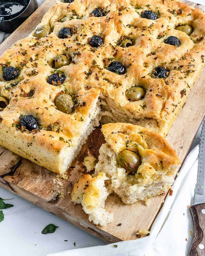 cooked Focaccia Bread with black and green olives with one slice cut on cutting board