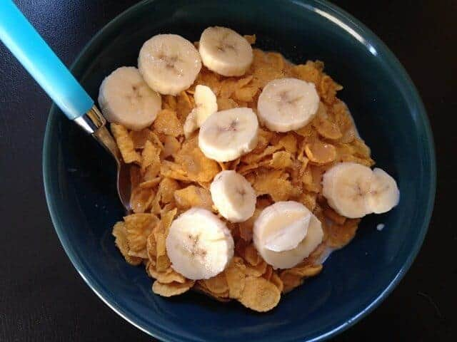 A blue bowl of cornflake cereal topped with sliced bananas.