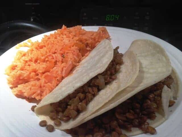 Two vegan tacos and a side of Spanish rice on a white plate.