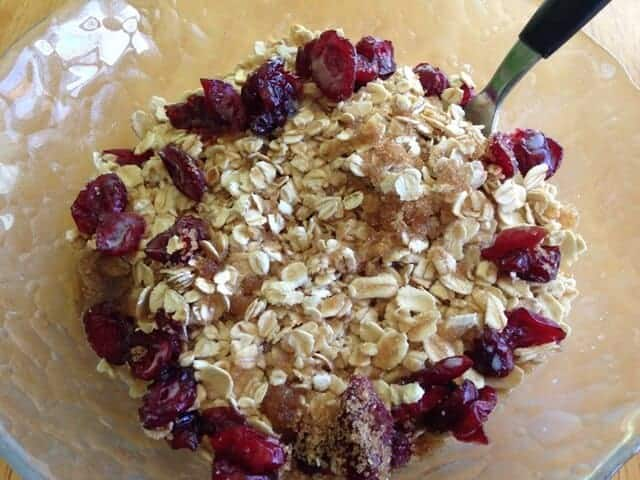 Oatmeal, dried cranberries, and soymilk in a glass bowl.