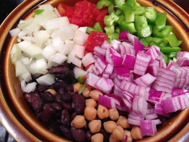 Chopped red onion, white onion, green peppers, and cooked beans in a brown bowl.
