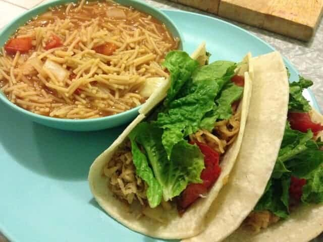 A small bowl of fideo pasta next to two sweet potato tacos.