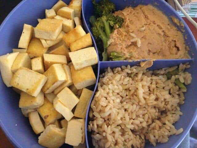 A divided dish containing cubed tofu, peanut sauce, and brown rice.