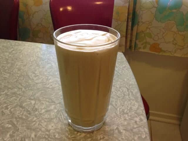 A glass of peanut butter banana smoothie on a table.