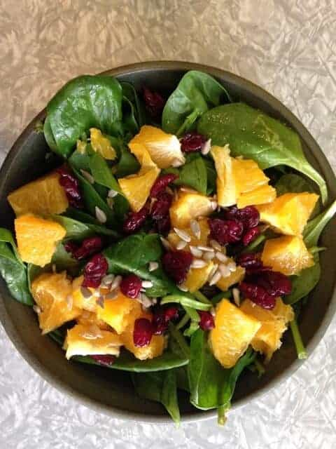 Bowl of spinach salad topped with peaches, cranberries, and sunflower seeds.