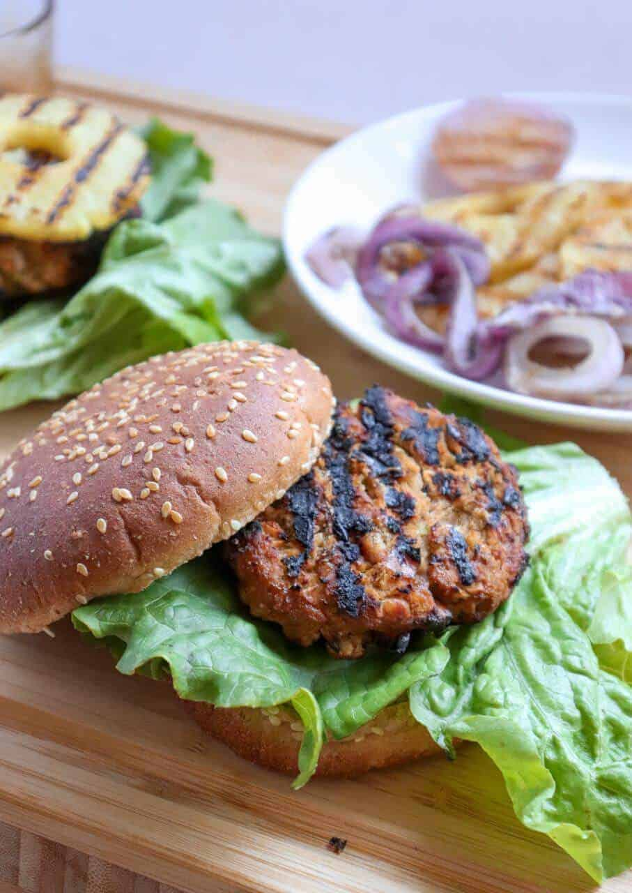 White Bean Teriyaki Burger with various ingredients on plates on a wood surface