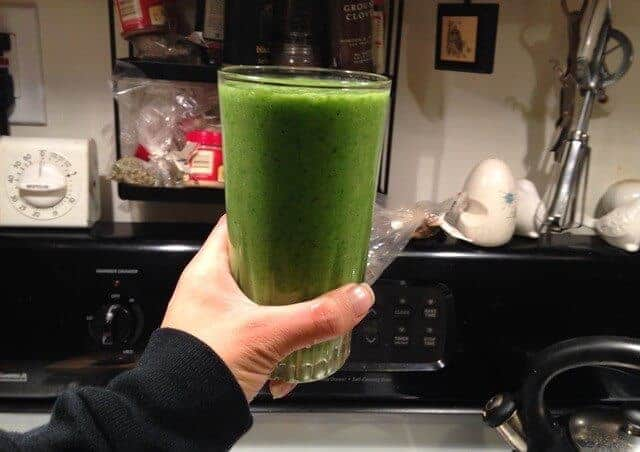 A hand holding a glass of banana kale smoothie.