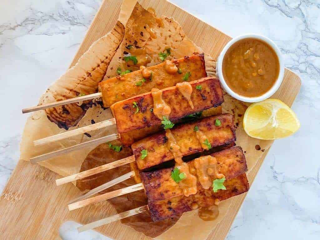 Oil-Free Tofu Satay with Peanut Sauce on a wooden board