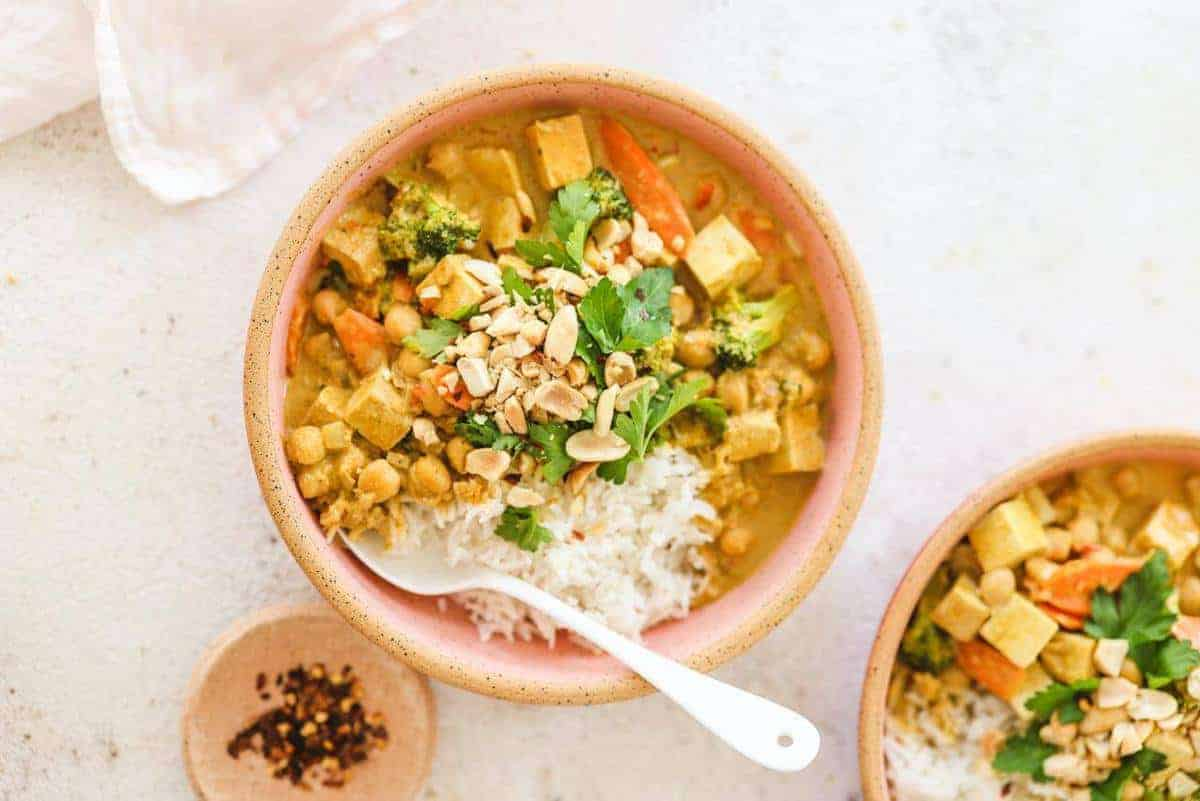 Peanut Curry in a pink bowl with a white spoon inside