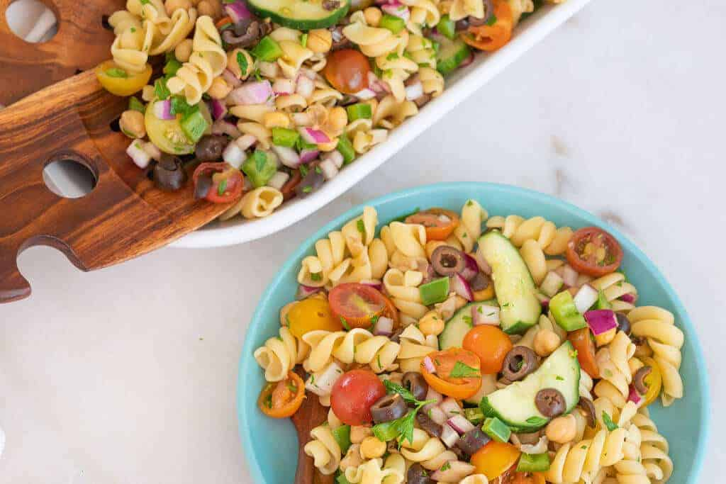 finished pasta salad in white tray and blue bowl against a white background