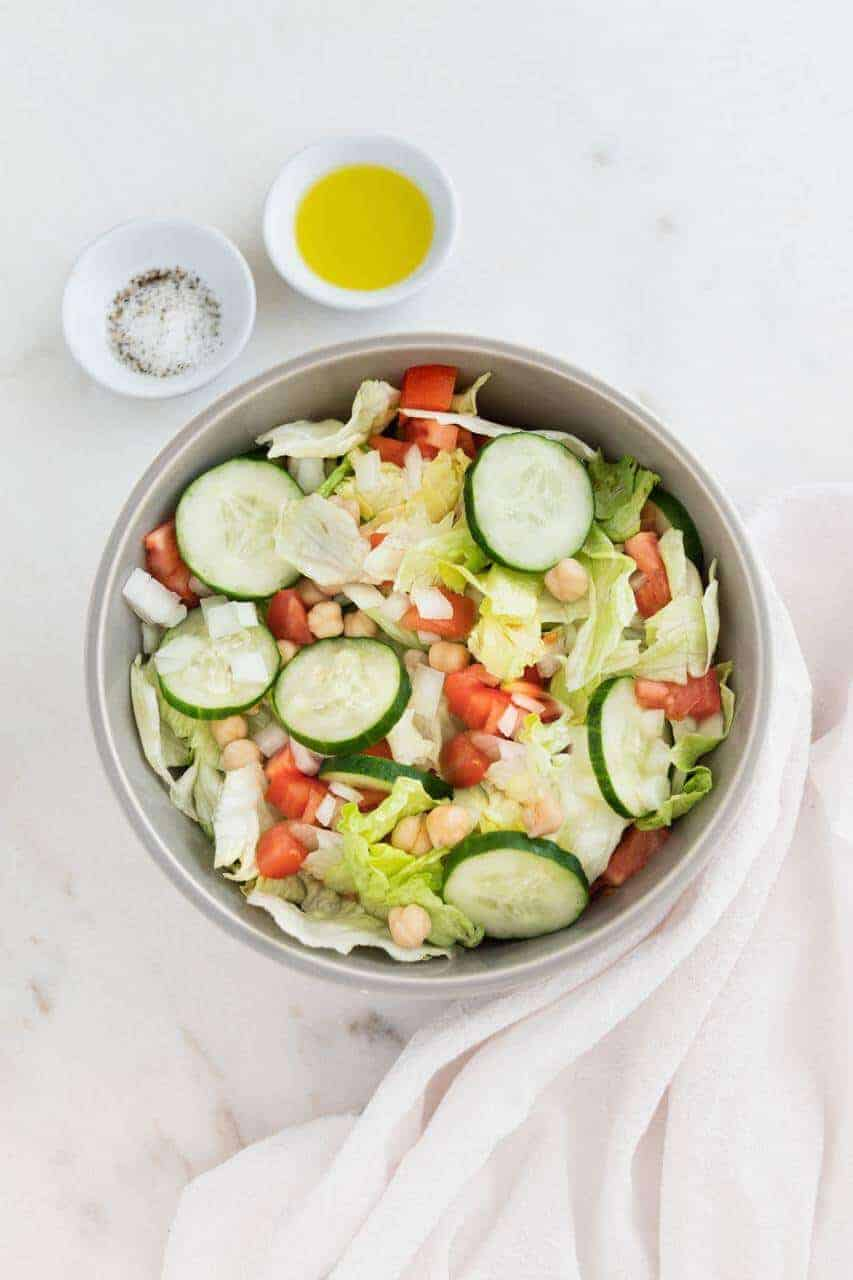 Fresh green salad with cucumbers, tomatoes, and garbanzo beans in a white bowl.
