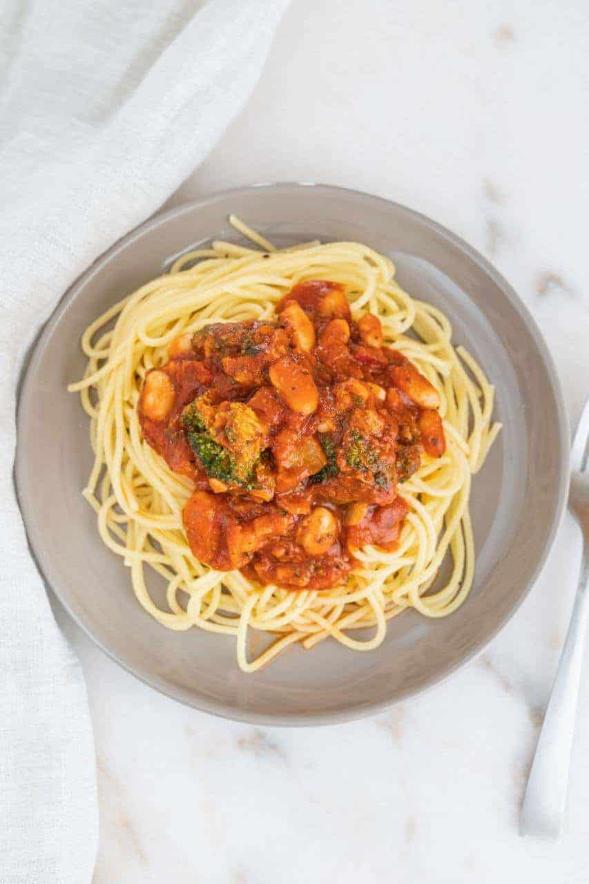Bean and veggie pasta sauce on a plate of spaghetti.