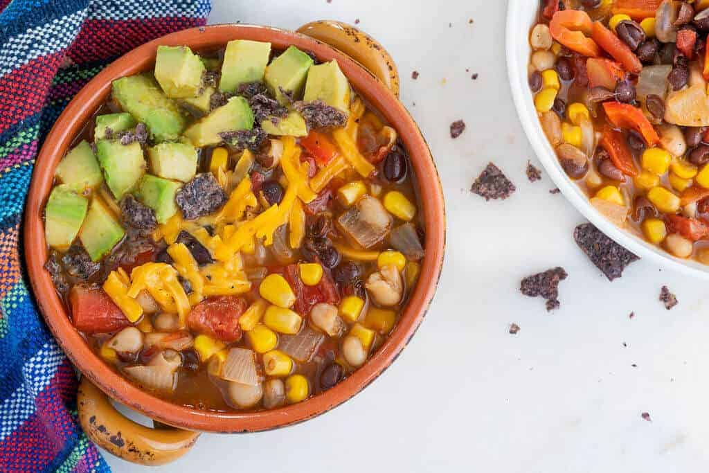 A ceramic bowl of southwestern soup topped with avocado and vegan cheese