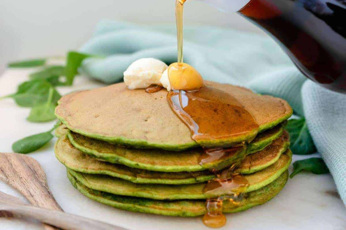 Stack of 4 green pancakes with a dollop of butter and maple syrup drizzling