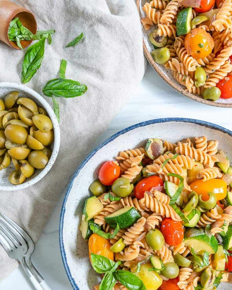white plate of pasta with veggies