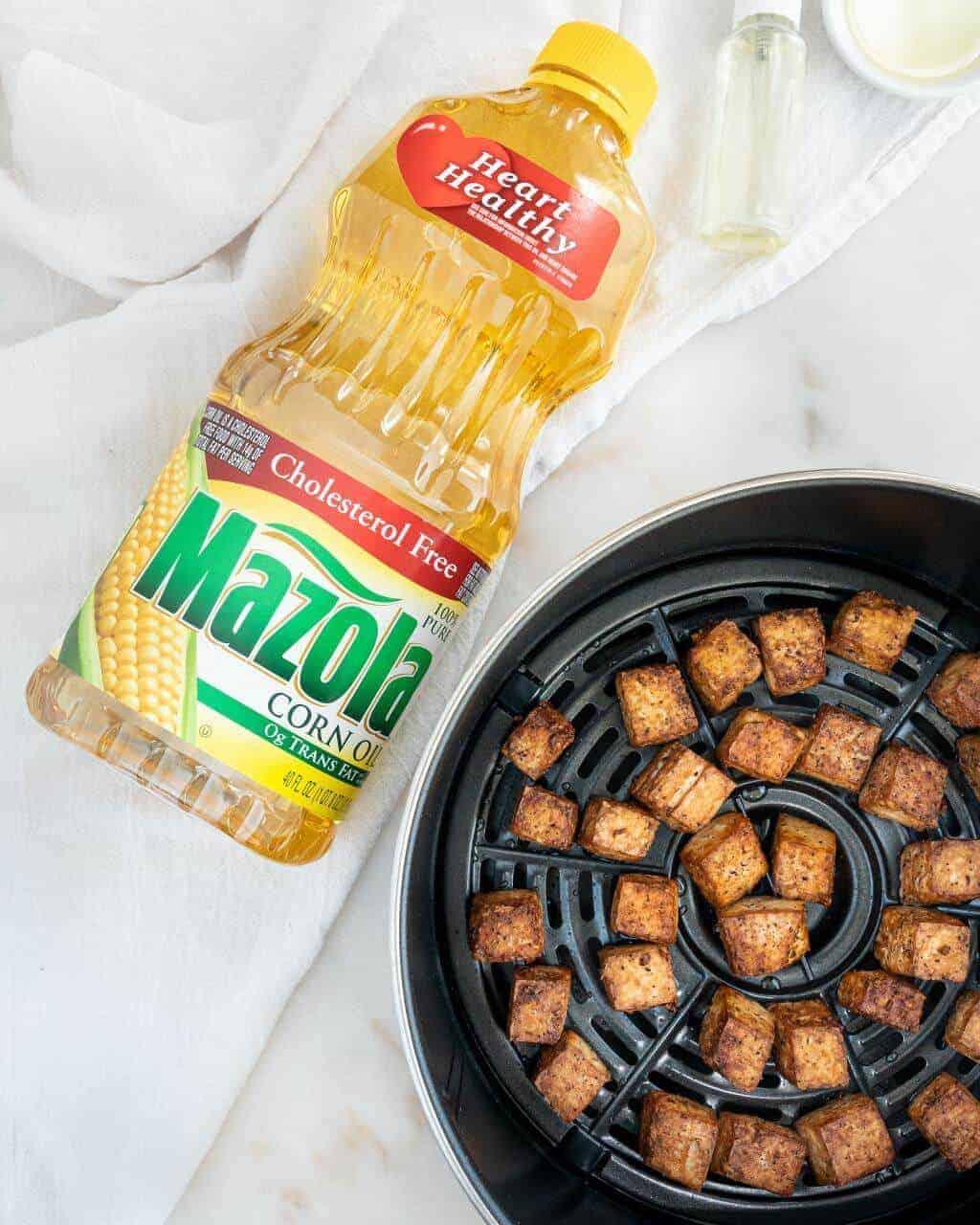 Bottle of Mazola Oil and Crispy Tofu inside an Air Fryer