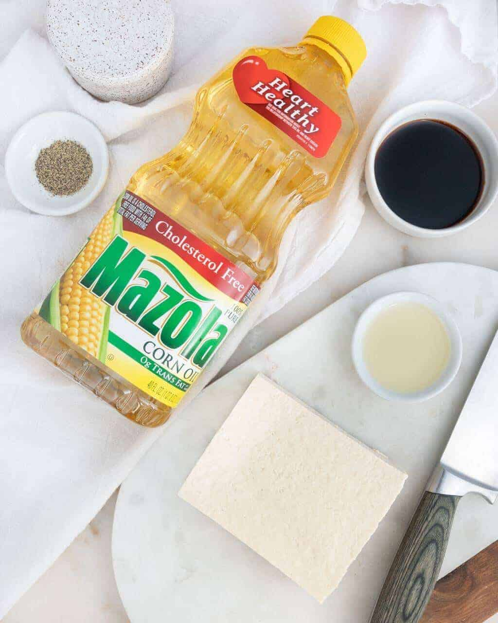 Bottle of Mazola Oil, Soy Sauce, a Block of Tofu, Salt and Pepper and a knife on a Wooden Board