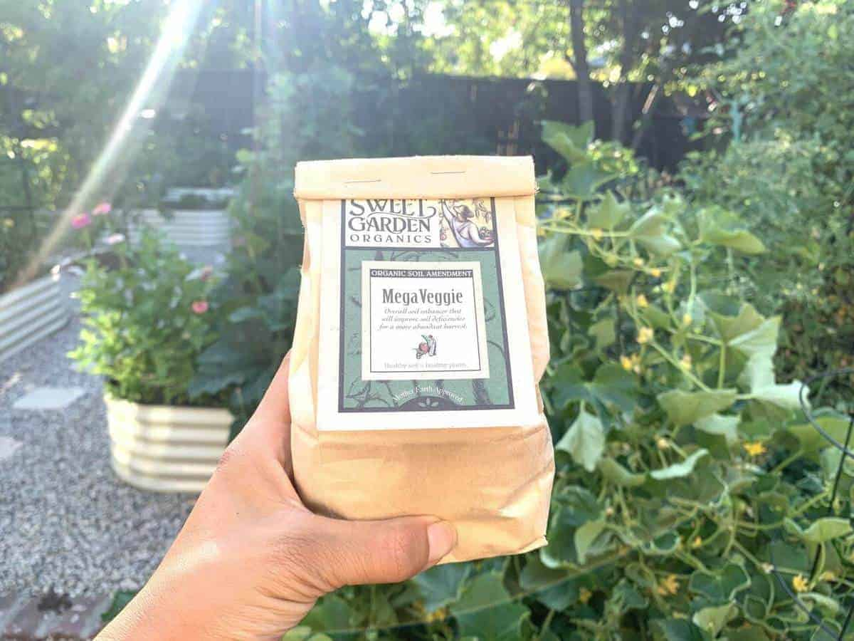 one brown bag of vegan fertilizer with a green leafy background