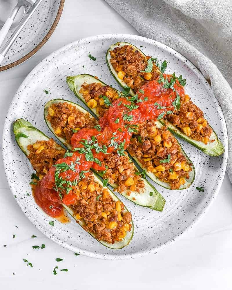 4 finished tex mex zucchini boats on a white plate with a white background