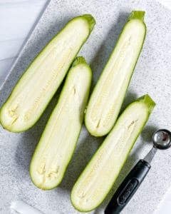 2 halved zucchinis with melon baller shown on cutting board
