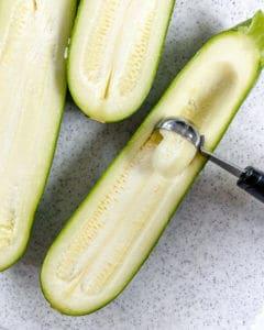process of using a melon baller on a zucchini