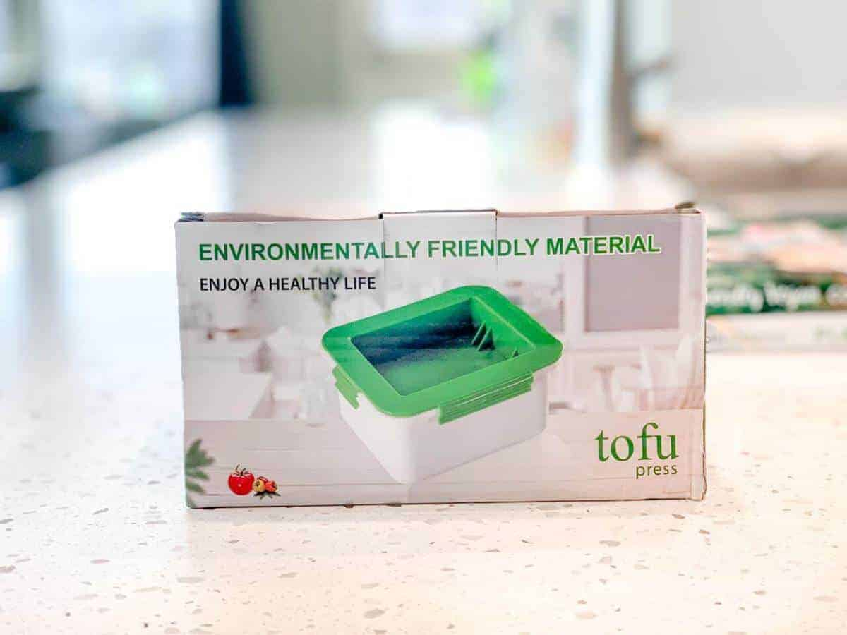 A tofu press in a box on a marble counter.