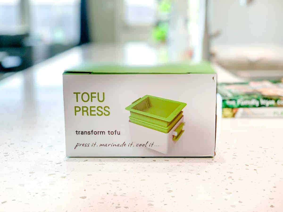 Tofu press in a box on a marble counter.