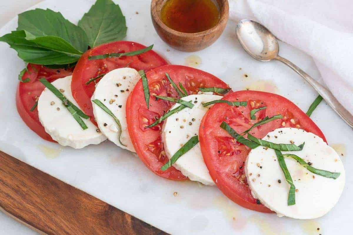 Marble Board with a Caprese salad drizzled with olive oil
