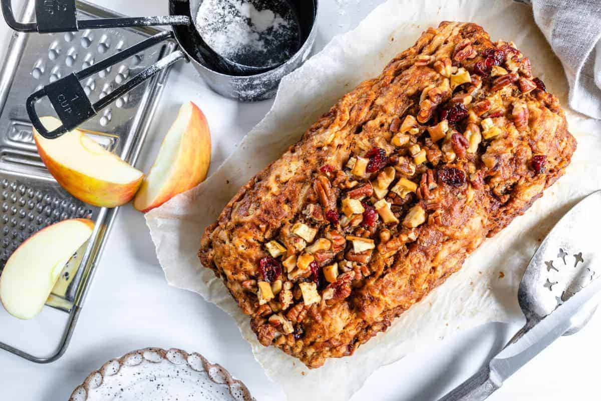 finished Apple Cinnamon Bread on a white surface with apples and gadgets in the background