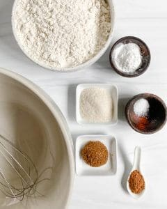 Various dry ingredients measured out against a white background