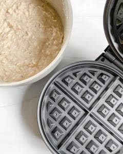 bowl of mixed batter and waffle iron against a white background