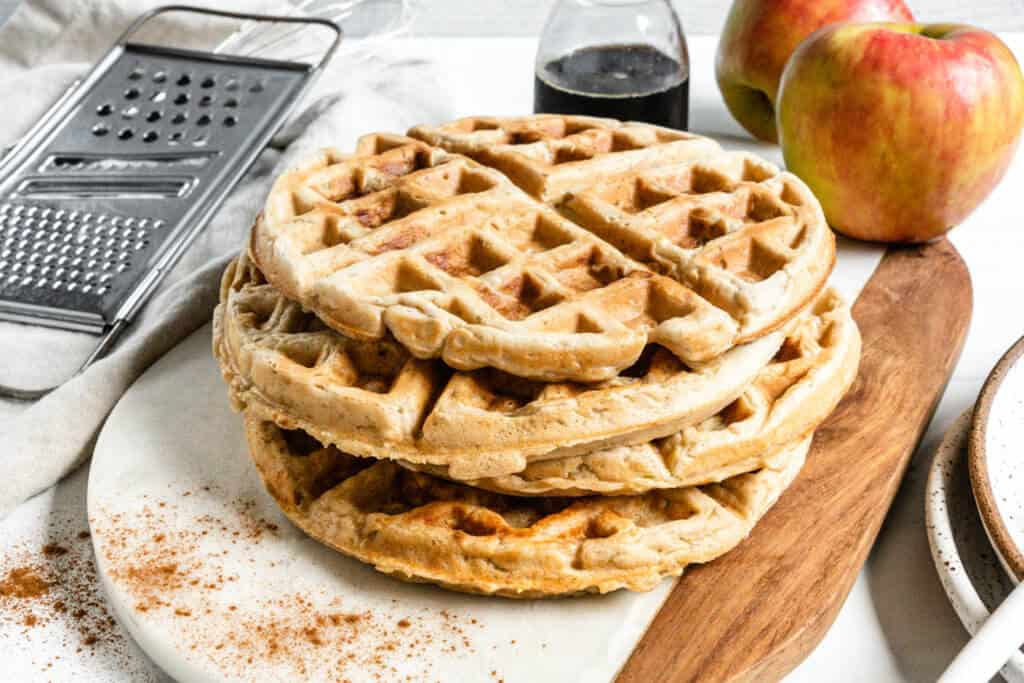 stack of Vegan Apple Cinnamon Waffles with apples and syrup in the background