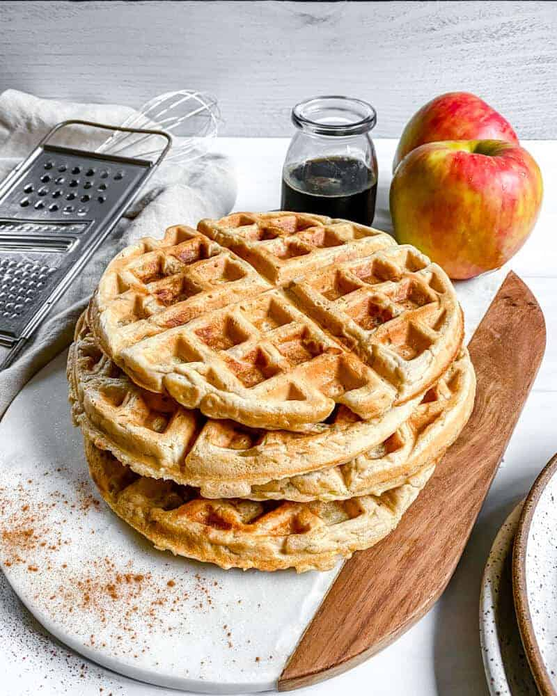 three finished Apple Cinnamon Waffles without syrup on a cutting board with apples and syrup in the background