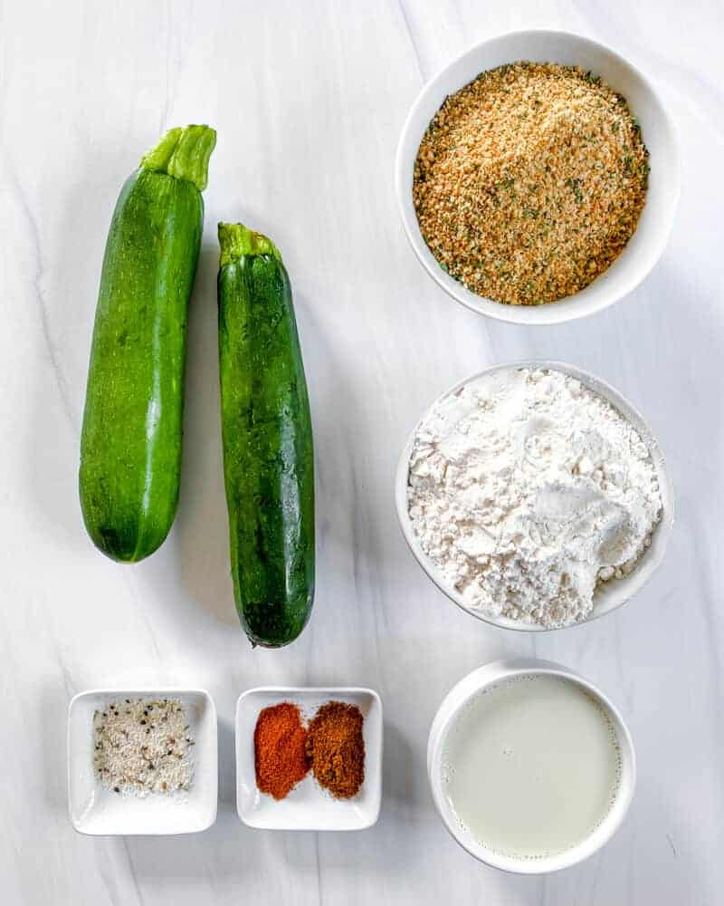 ingredients for Baked Zucchini Fries in a white background