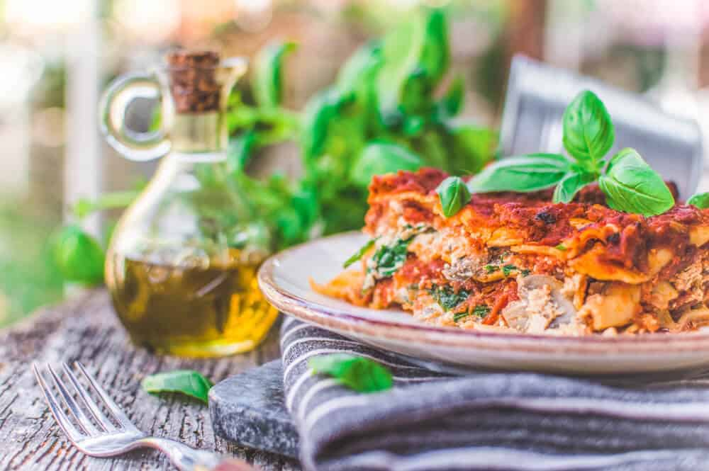 plate of vegan lasagna on gray cloth with a glass filled with a yellow drink and fresh herbs in the background
