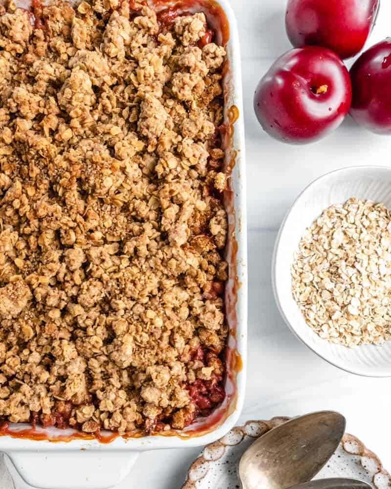 vegan plum crisp with ingredients in a white background